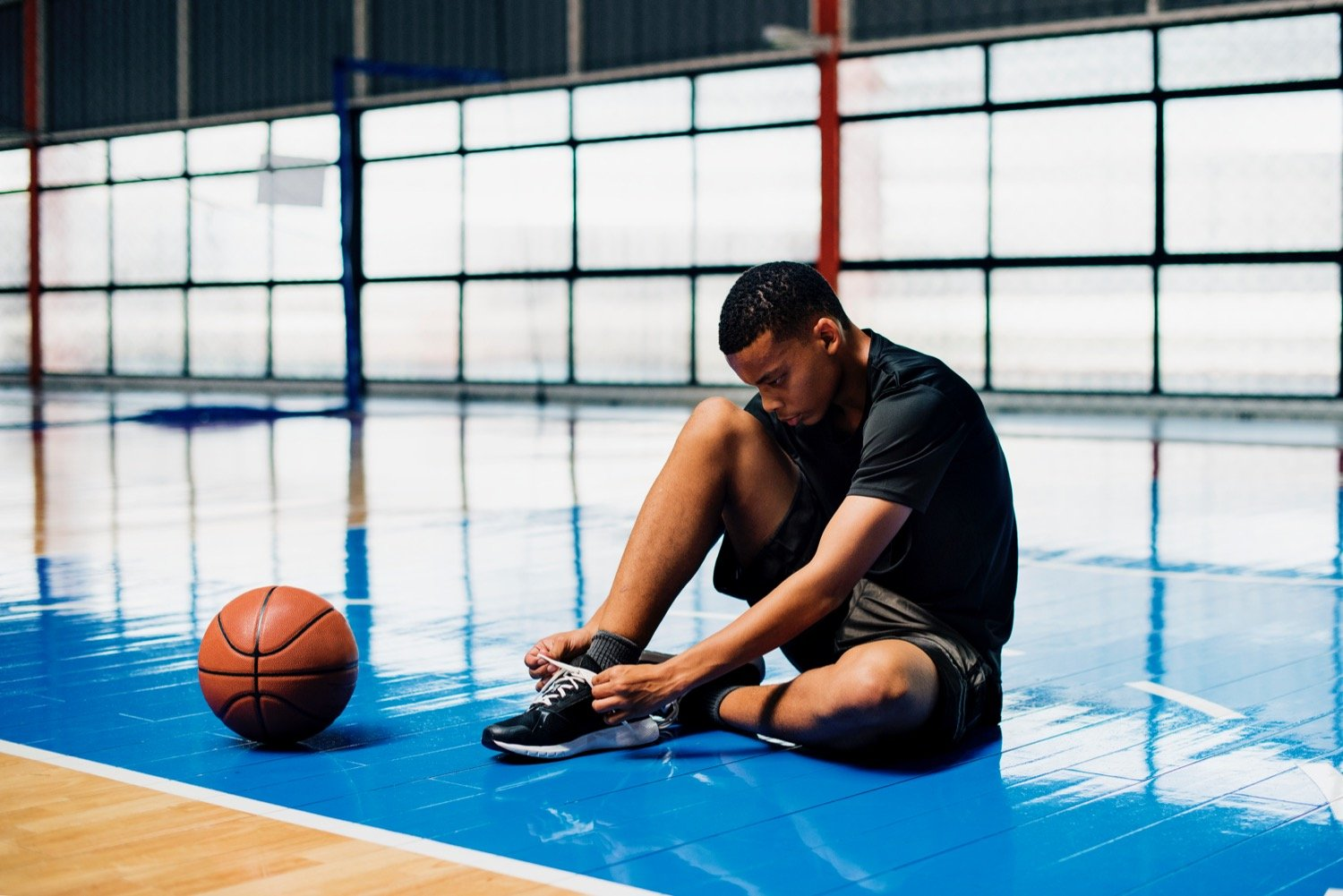 Young Basketball Player on Court Adjusting Foot Orthotics