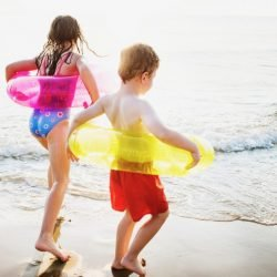 Two Young Kids Running on Beach Before Healthy Foot Checkup