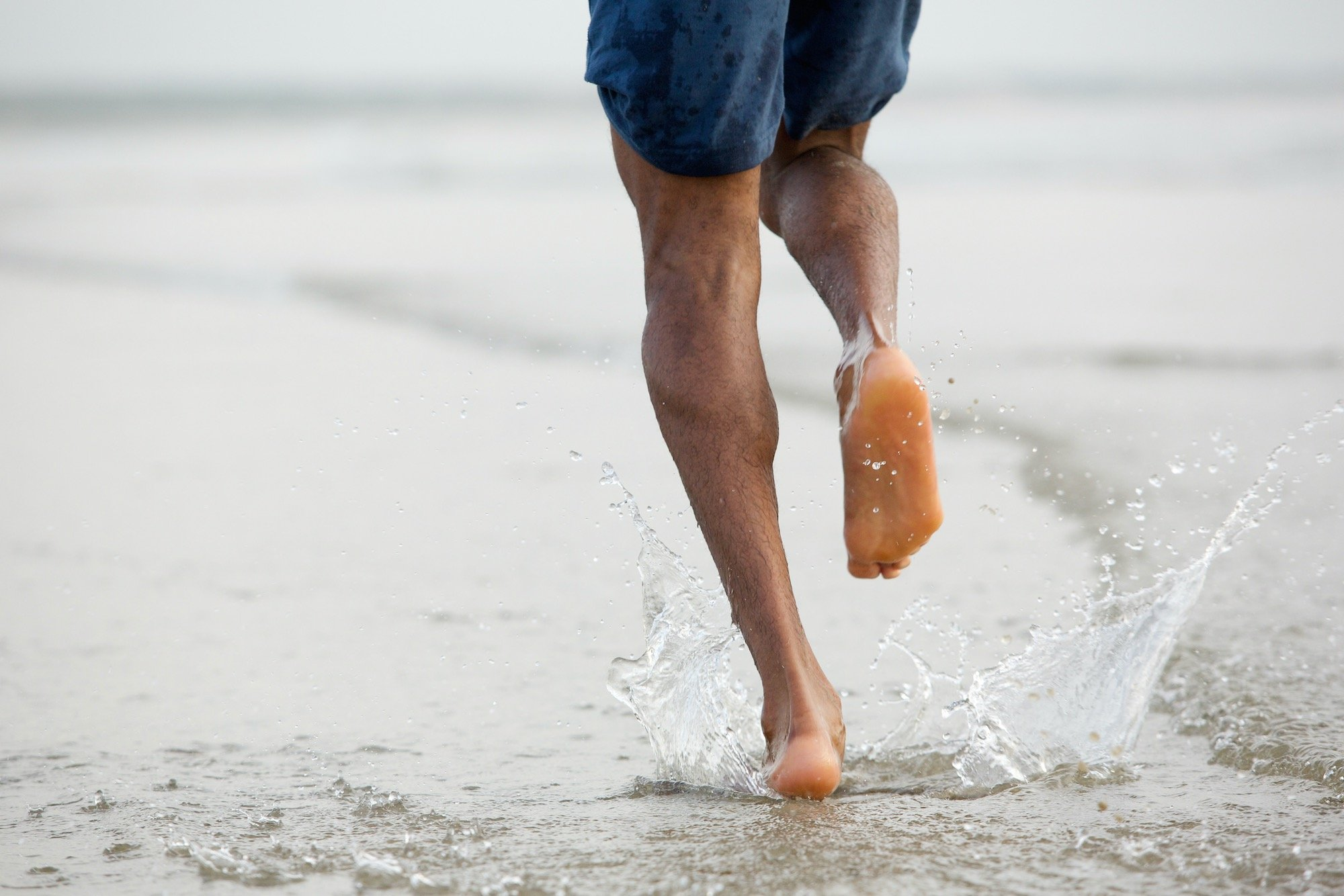 Man Running on Beach to Relieve Foot Pain