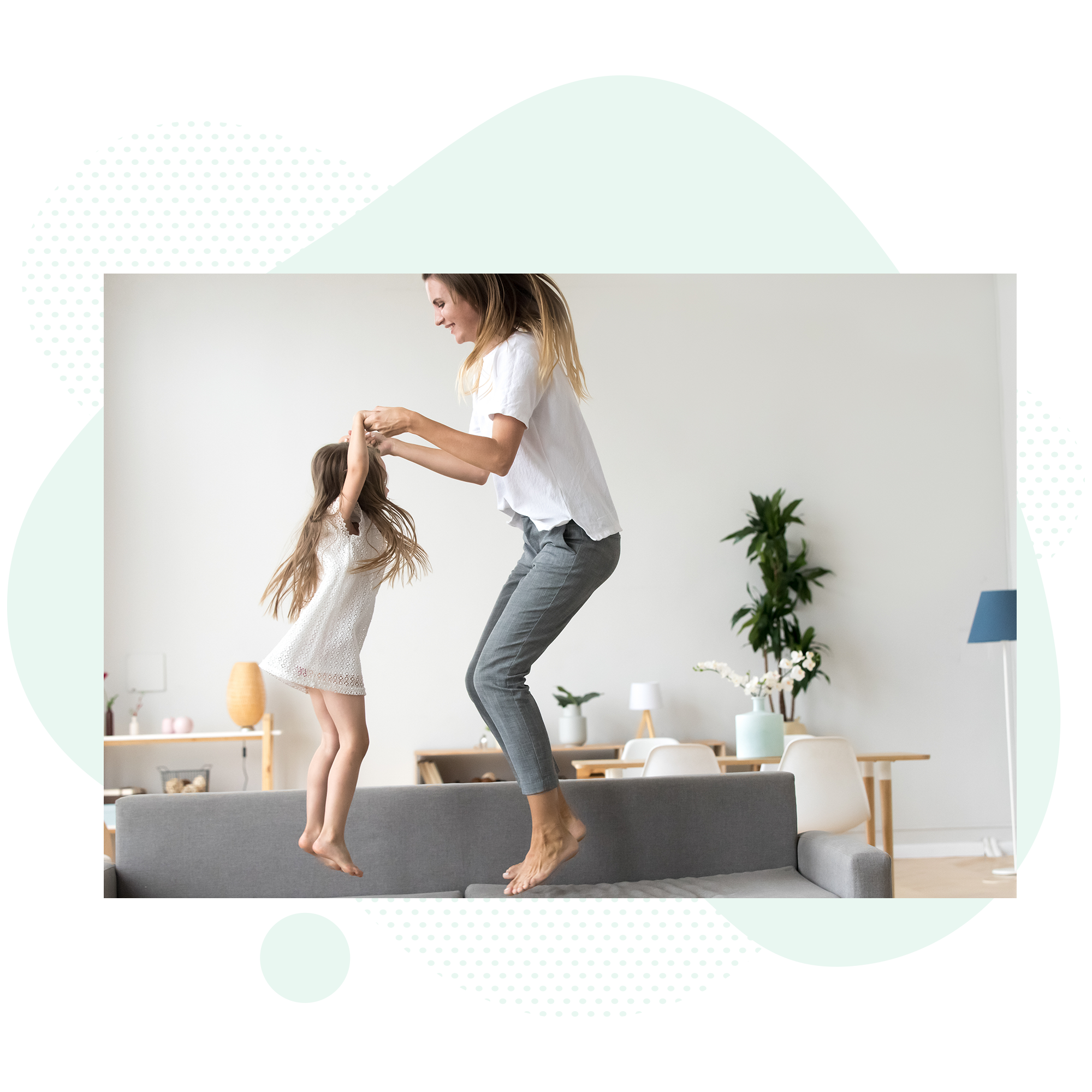 Mom and daughter jumping on a couch