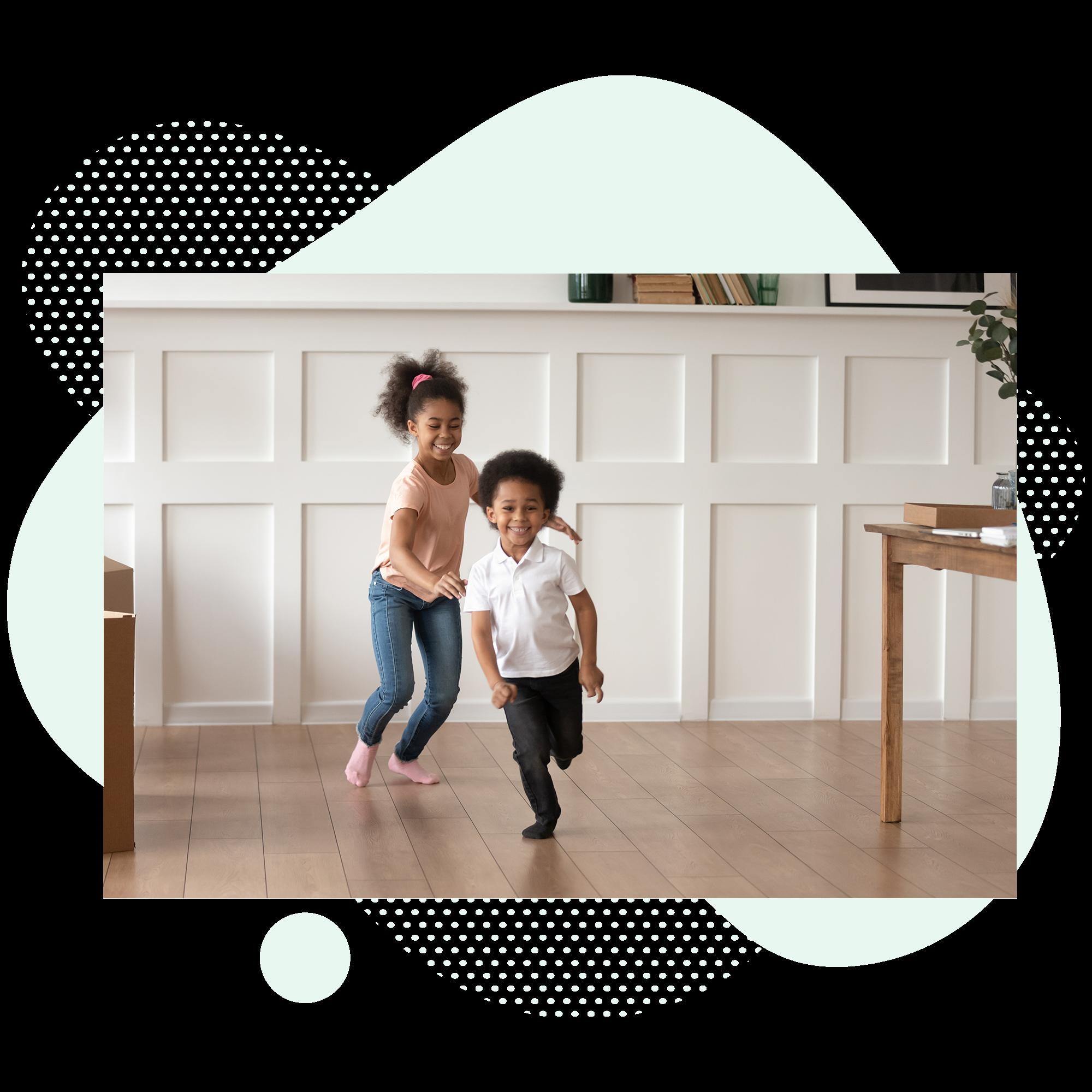 Two kids running down a hallway