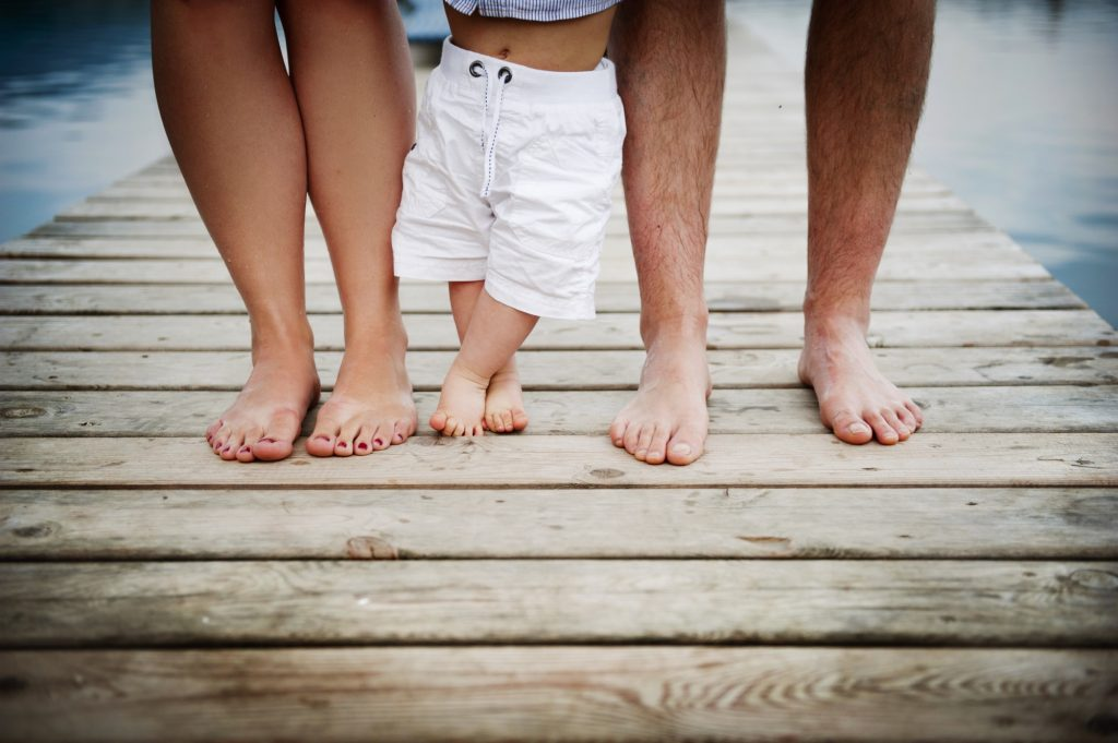 Young Family Standing on Dock Addressing Baby's Foot Pain