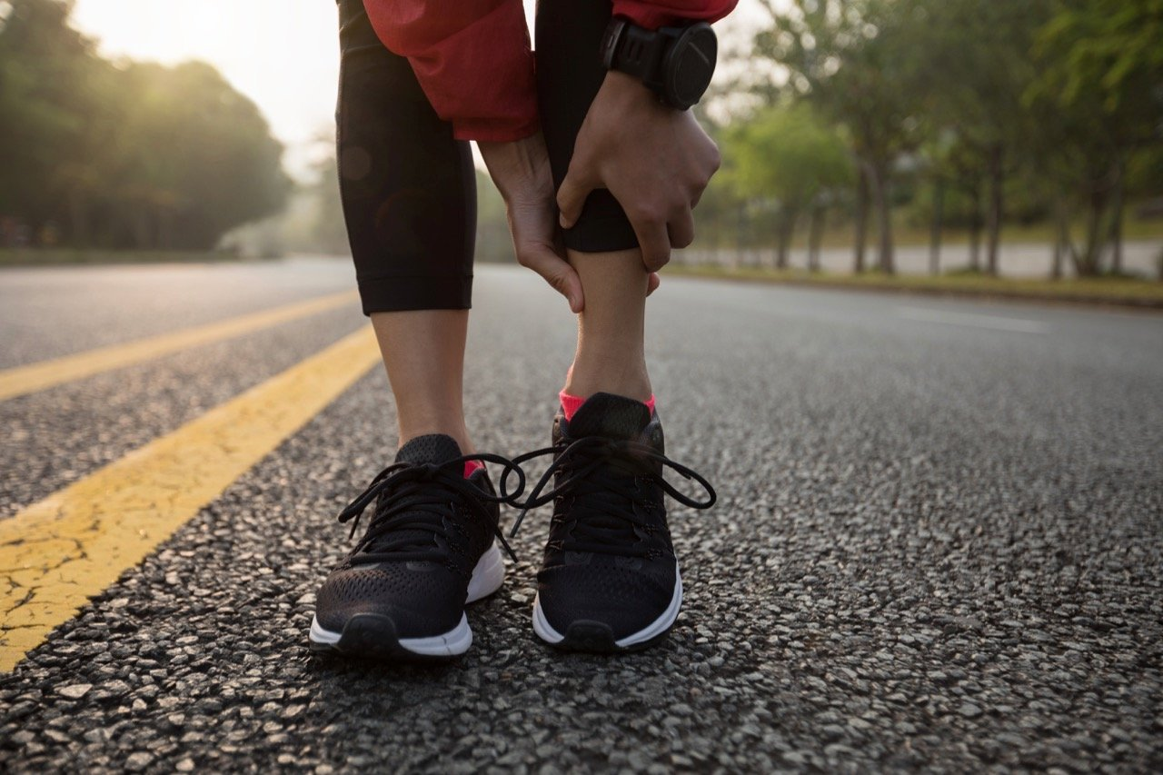 Young Woman Jogging on Street Holding Sport Injury