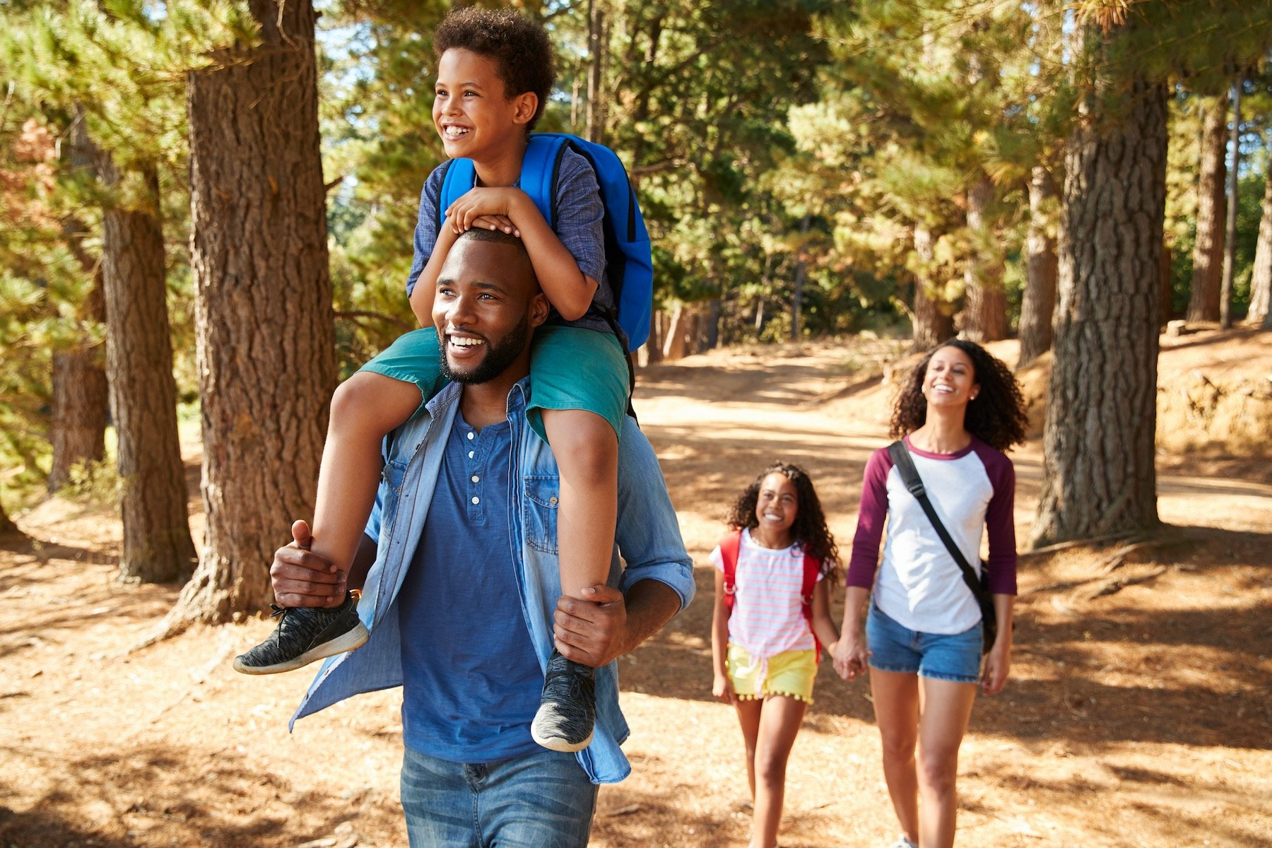 FAMILY HIKING THROUGH THE FOREST CHEERFULLY