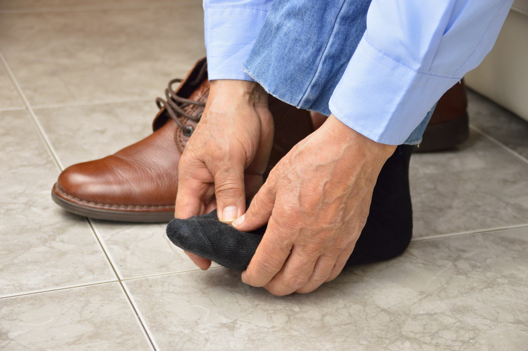 OLDER MAN HOLDING HIS FOOT IN PAIN